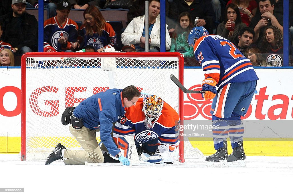 Richard Bachman #30 of the Edmonton Oilers receives medical attention after sustaining an injury in a game against the Detroit Red Wings on November 2, 2013 at Rexall Place in Edmonton, Alberta, Canada.