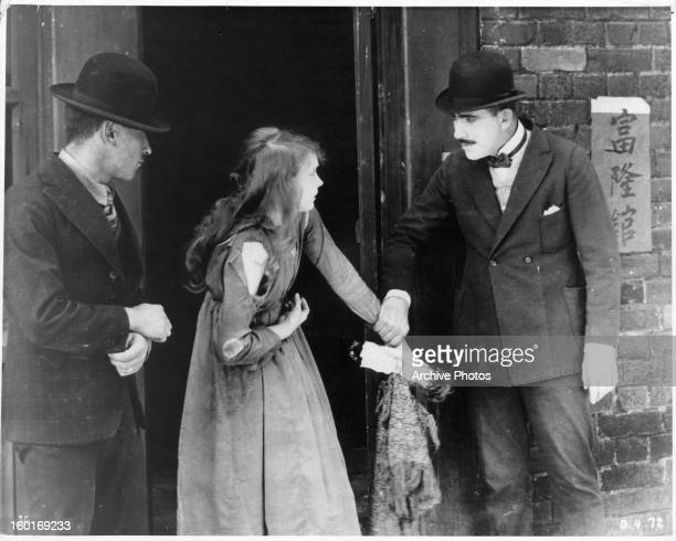 Richard Barthelmess and Lillian Gish encounter a man in a scene from the film 'Broken Blossoms' 1919