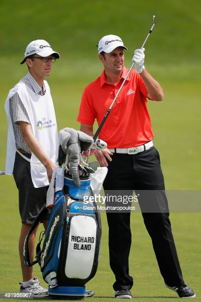 Richard Bland of England speaks to his caddie and selects a club before he hits his second shot on the 1st hole during the final round of the Open de...