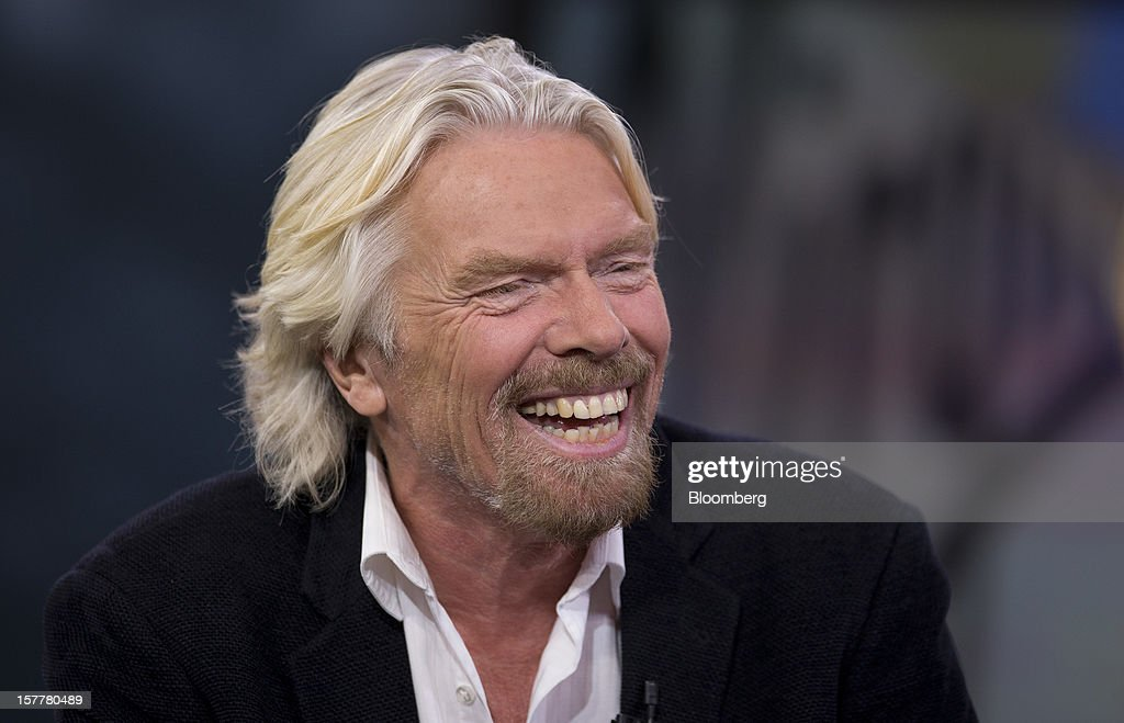 Richard Branson, chairman and founder of Virgin Group Ltd., laughs during an interview in New York, U.S., on Thursday, Dec. 6, 2012. Branson's Virgin Trains was handed a deal to run Britain's premier rail route for two more years on the day a government-backed probe found that a decision to strip it of the contract was based on faulty calculations. Photographer: Scott Eells/Bloomberg via Getty Images