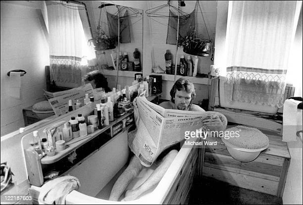 Richard Branson reading the newspaper in the bath on his boat at Little Venice