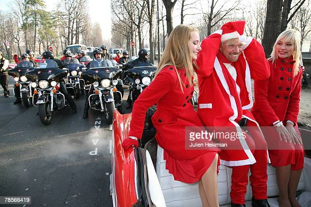 Richard Branson wearing a Santa suit travels in a sports car along the ChampsElysees Avenue passing the landmark Arc de Triomphe on December 19 2007...