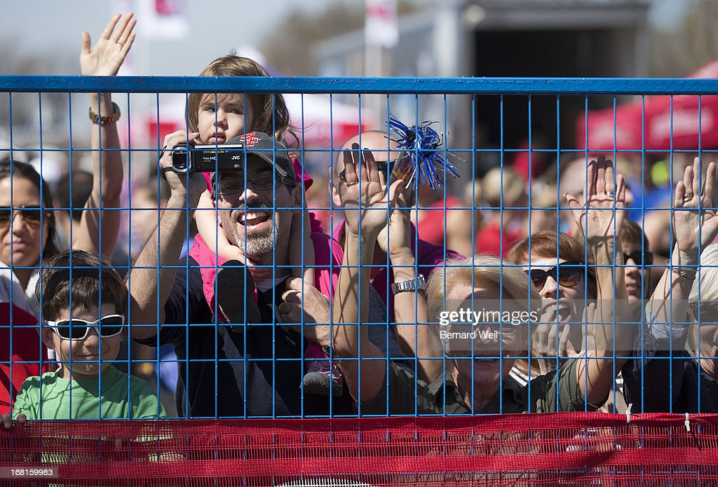 Richard Castro (holding video camera) video tapes his wife Nadia coming heading to the finish in the Toronto Marathon, while daughter Shaela, 3 (on shoulders), son Sebastian, 4 (left) and mother Jose Castro cheer on.