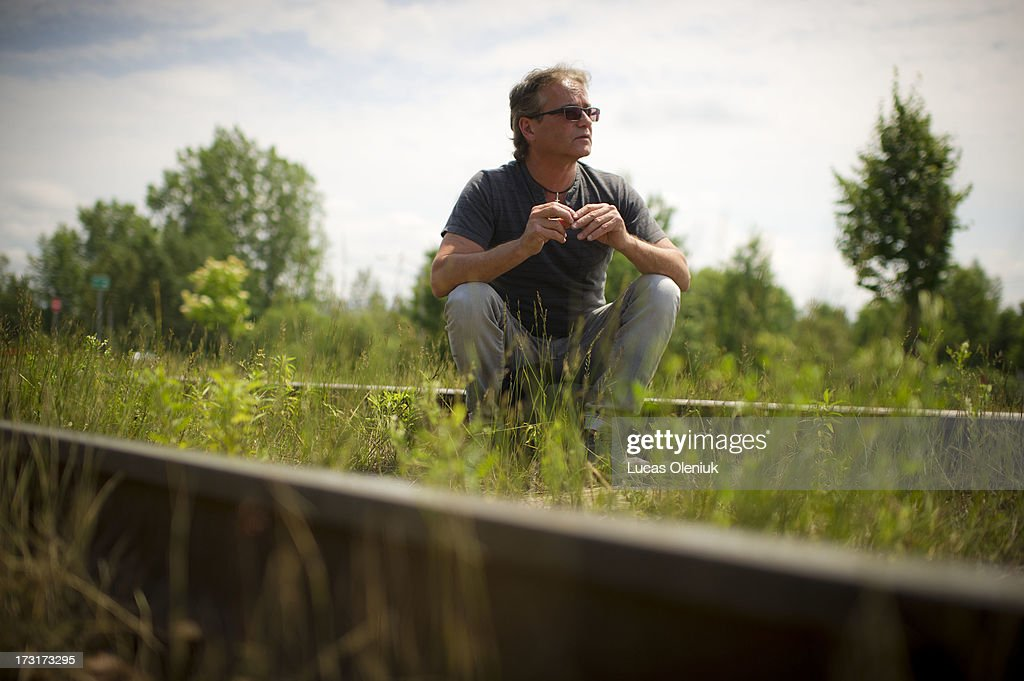 Richard Custeau sits on the rail that leads to downtown Lac-MÈgantic where his brother, RÈal Custeau, lived before the derailment explosion leveled the town centre. RÈal Custeau is still missing and search crews are scouring the rouble where his apartment once stood.