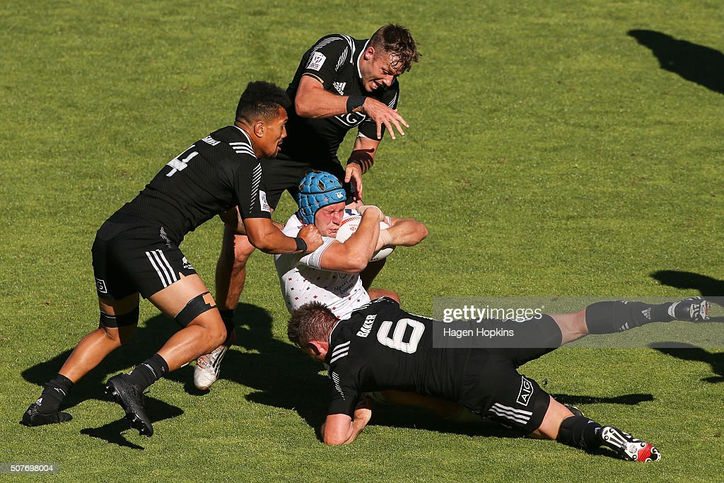 Richard de Carpentier of England is tackled by <a gi-track='captionPersonalityLinkClicked' href=/galleries/search?phrase=Ardie+Savea&family=editorial&specificpeople=8836502 ng-click='$event.stopPropagation()'>Ardie Savea</a>, Kurt Baker and <a gi-track='captionPersonalityLinkClicked' href=/galleries/search?phrase=Tim+Mikkelson&family=editorial&specificpeople=5366047 ng-click='$event.stopPropagation()'>Tim Mikkelson</a> of New Zealand during the 2016 Wellington Sevens cup semi-final match between New Zealand and England at Westpac Stadium on January 31, 2016 in Wellington, New Zealand.