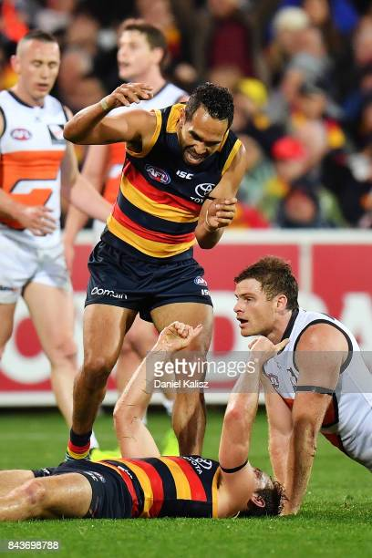Richard Douglas and Eddie Betts of the Crows celebrate the score of a goal as Heath Shaw of the Giants looks on dejected during the AFL First...