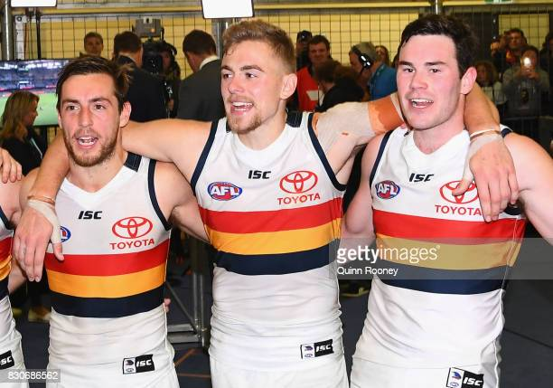 Richard Douglas Hugh Greenwood and Mitchell McGovern of the Crows sing the song in the rooms after winning the round 21 AFL match between the...