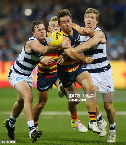 Richard Douglas of the Crows compete for the ball against Mitch Duncan of the Cats and Scott Selwood during the round 11 AFL match between the...
