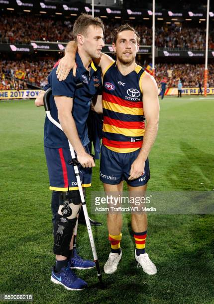 Richard Douglas of the Crows consoles an injured Brodie Smith of the Crows who will miss the grand final during the 2017 AFL First Preliminary Final...
