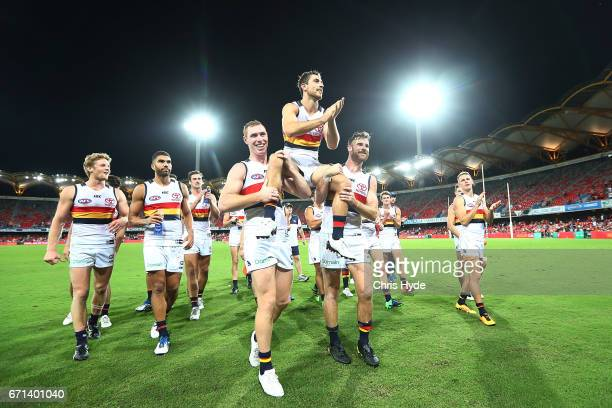 Richard Douglas of the Crows is chaired from the field after playing his 200th match during the round five AFL match between the Gold Coast Suns and...