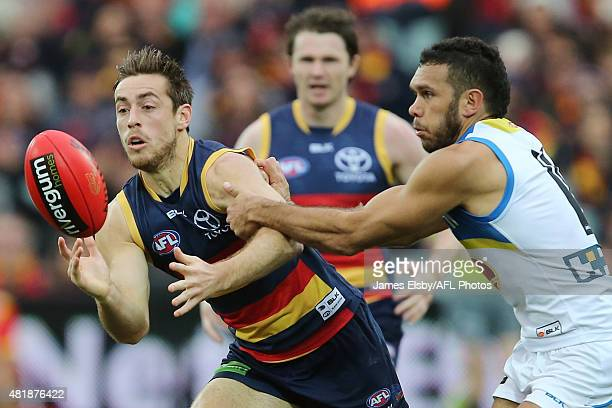 Richard Douglas of the Crows is tackled by Harley Bennell of the Suns during the 2015 AFL round 17 match between the Adelaide Crows and the Gold...