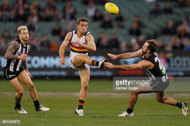 Richard Douglas of the Crows kicks the ball past Steele Sidebottom of the Magpiesduring the round 19 AFL match between the Collingwood Magpies and...