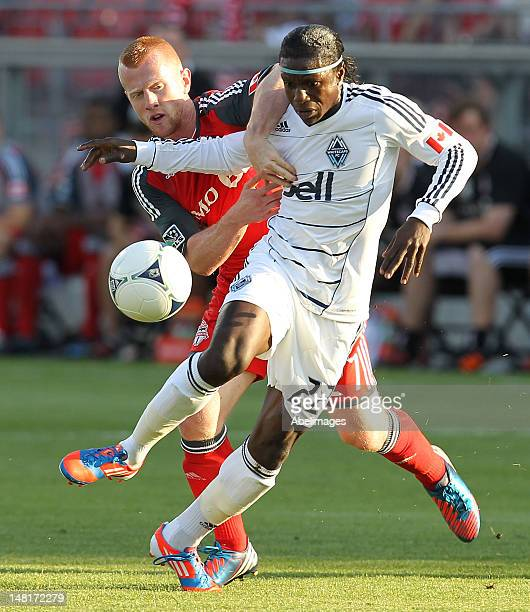 Richard Eckersley of Toronto FC battles for the ball with Darren Mattocks of the Vancouver Whitecaps during MLS action at the BMO Field July 11 2012...