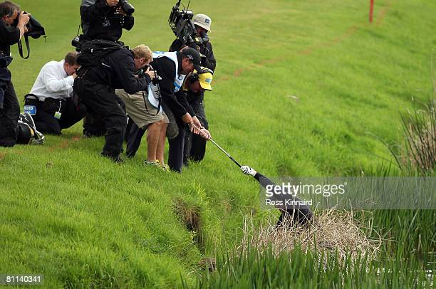 Richard Finch of England is helped out of the river Maigue by his caddie Damian Moore after his second shot to the par five 18th hole during the...