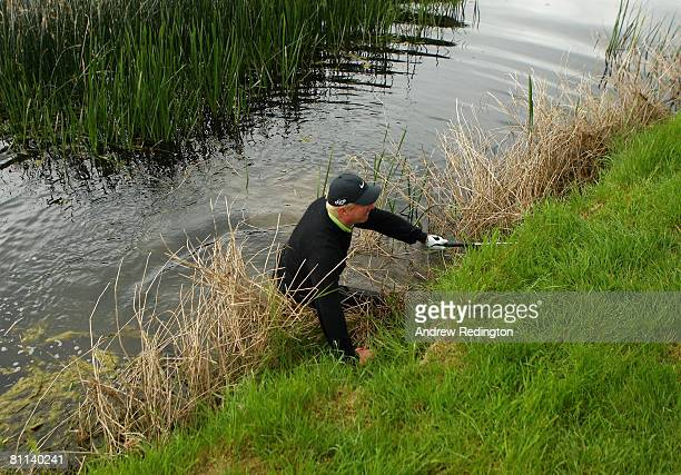 Richard Finch of England scrambles out of the river Maigue after falling in it after hitting his third shot on the 18th hole during the final round...
