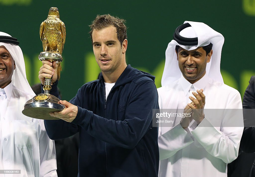 Richard Gasquet of France lifts the trophy and poses with Nasser Al-Khelaifi, President of the Qatar Tennis Federation and President of Paris Saint-Germain, after defeating in the final Nikolay Davydenko of Russia in day six of the Qatar Open 2013 at the Khalifa International Tennis and Squash Complex on January 5, 2013 in Doha, Qatar.