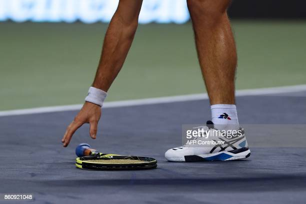 Richard Gasquet of France picks up his racquet during the men's quarterfinals singles match against Roger Federer of Switzerland at the Shanghai...