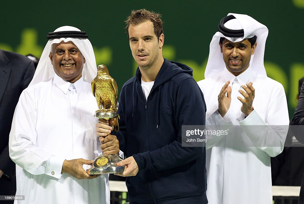 Richard Gasquet of France (C) receives the trophy from Abdulla Bin Hamad Al Attiyah, Deputy Prime Minister of Qatar (L) and Nasser Al-Khelaifi (R), President of the Qatar Tennis Federation and President of Paris Saint-Germain after defeating Nikolay Davydenko of Russia in the final on day six of the Qatar Open 2013 at the Khalifa International Tennis and Squash Complex on January 5, 2013 in Doha, Qatar.