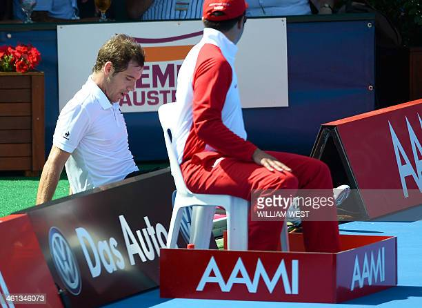Richard Gasquet of France sits on the ground after tripping over a sign in his match with Jordan Thompson of Australia at the invitational Kooyong...