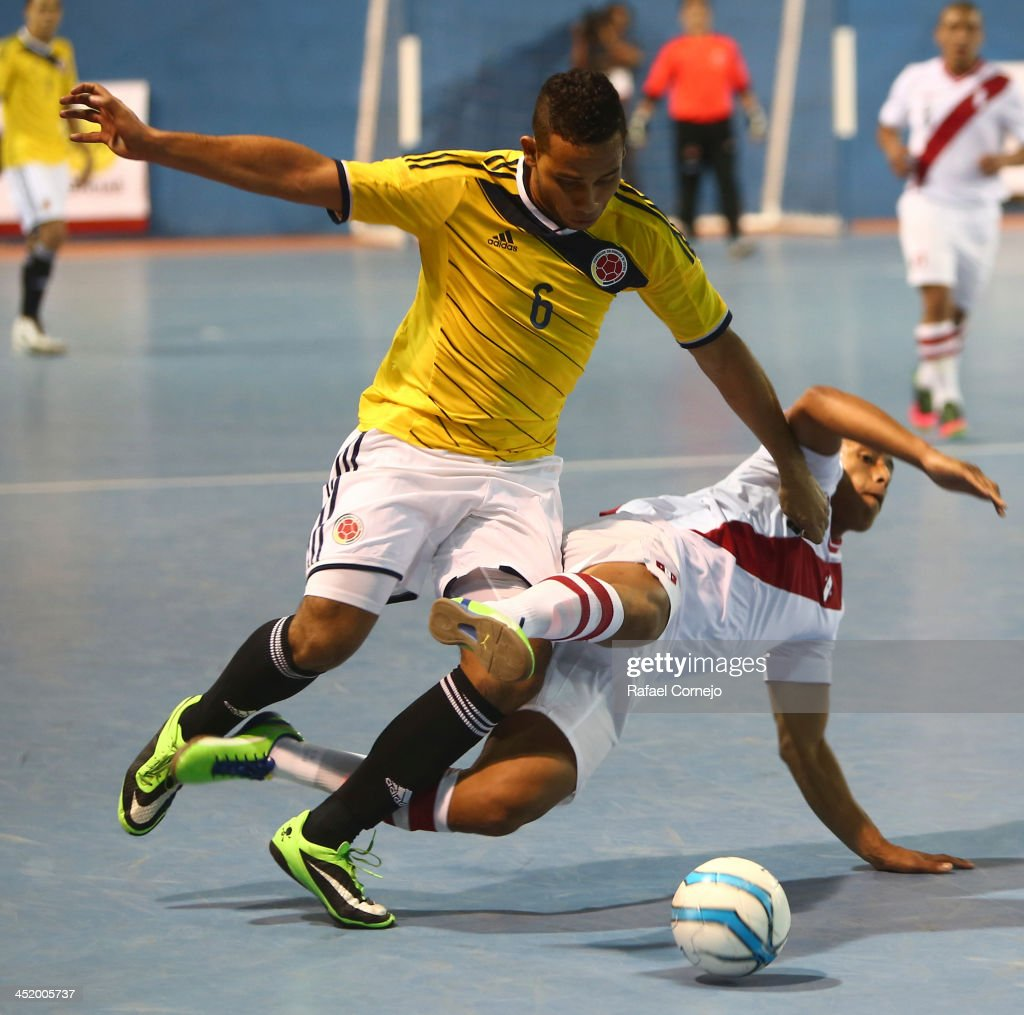 Richard Gutierrez of Colombia fights for the ball with Jesus Suarez of Peru during a match between Colombia and Peru as part of the XVII Bolivarian Games Trujillo 2013 at Videna San Luis on November 25, 2013 in Lima, Peru.