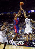 Richard Hamilton of the Detroit Pistons scores over Jameer Nelson and past Dwight Howard of the Orlando Magic late in the game to give the Pistons a...