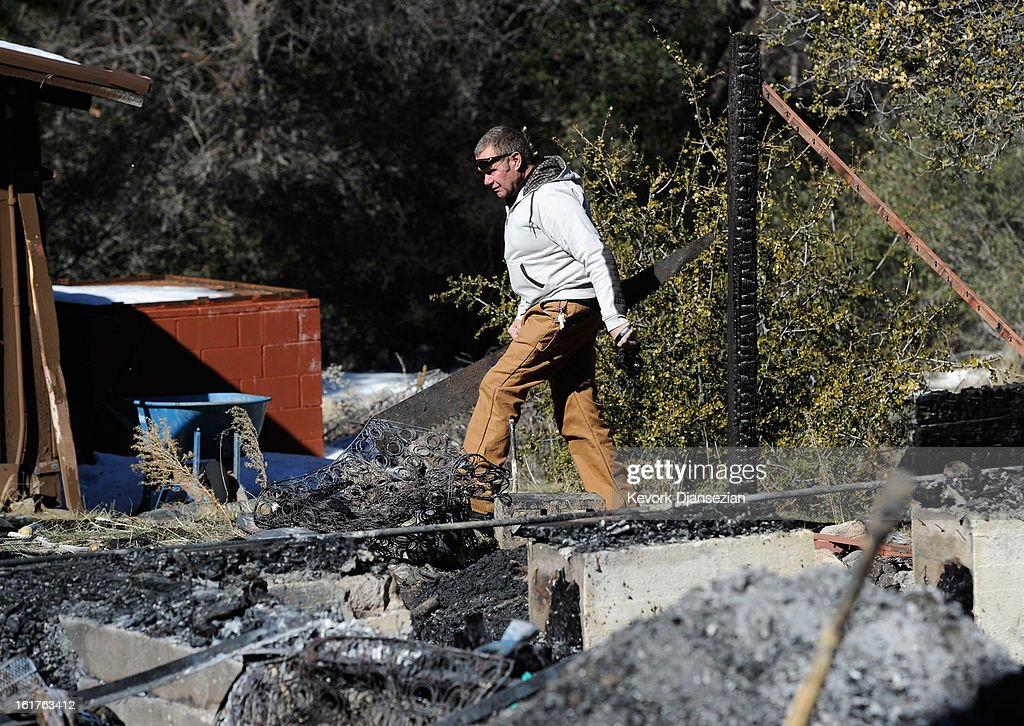 Richard Heltebrake, whose truck was carjacked by multiple murder suspect and former Los Angeles Police Department officer Christopher Dorner, carries handsaw near the burned out cabin where the remains of Dorner were found is seen on February 15, 2013 in Big Bear, California. Dorner, a former Los Angeles Police Department officer and Navy Reserve veteran, barricaded himself in the cabin near Big Bear, California, and engaged law enforcement officers in shootout, shooting two police, killing one and wounding the other. Dorner's, who's body was identified after being found, was wanted in connection with the deaths of an Irvine couple and a Riverside police officer.
