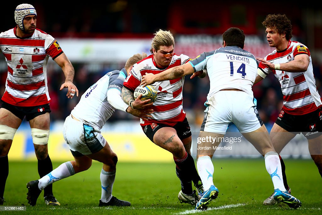 Richard Hibbard of Gloucester is tackled by Giamba Venditti and Chris Harris of Newcastle during the Aviva Premiership match between Gloucester Rugby...