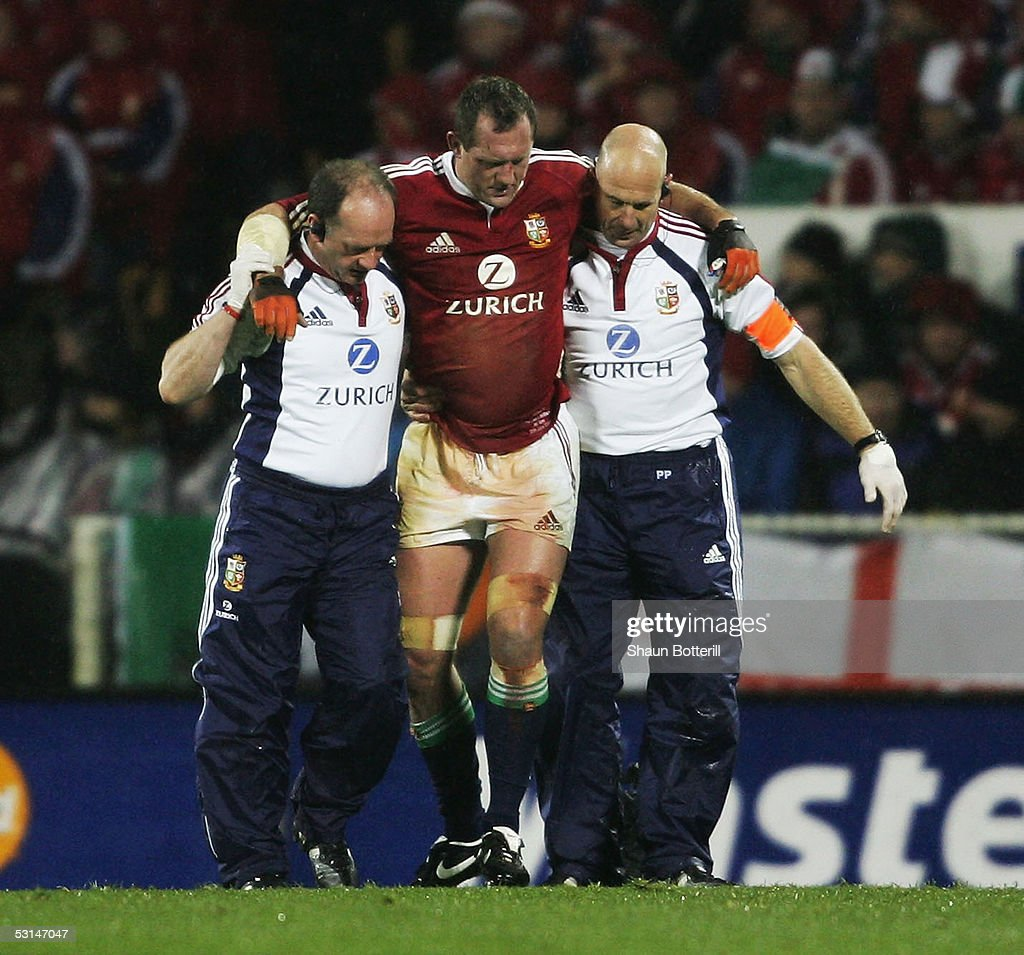 Richard Hill of the Lions leaves the field with Doctor James Robson and Physio Phil Pask during the first test match between New Zealand All Blacks...