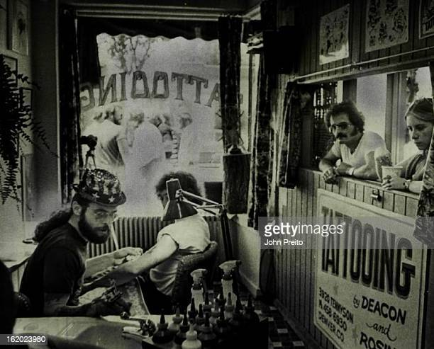 AUG 11 1977 AUG 17 1977 Richard Hincher Sneakin Deacon Works In His Colorful North Denver Shop Two persons watch an application in the tattoo shop a...