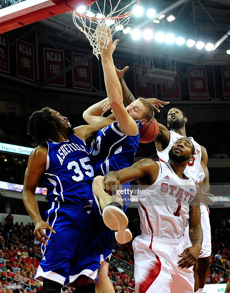 Richard Howell #1 and C.J. Leslie #5 of the North Carolina State Wolfpack battle for a rebound with Jon Nwannunu #35 and D.J. Cunningham #33 of the North Carolina-Asheville Bulldogs during play at PNC Arena on November 23, 2012 in Raleigh, North Carolina.