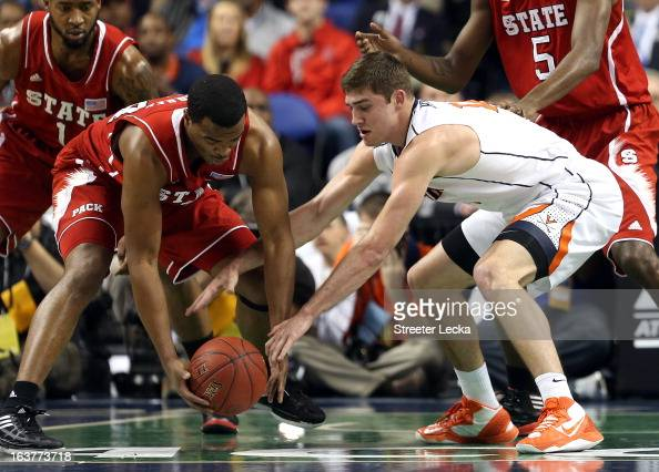 Richard Howell of the North Carolina State Wolfpack battles for a loose ball with Joe Harris of the Virginia Cavaliers during the quarterfinals of...