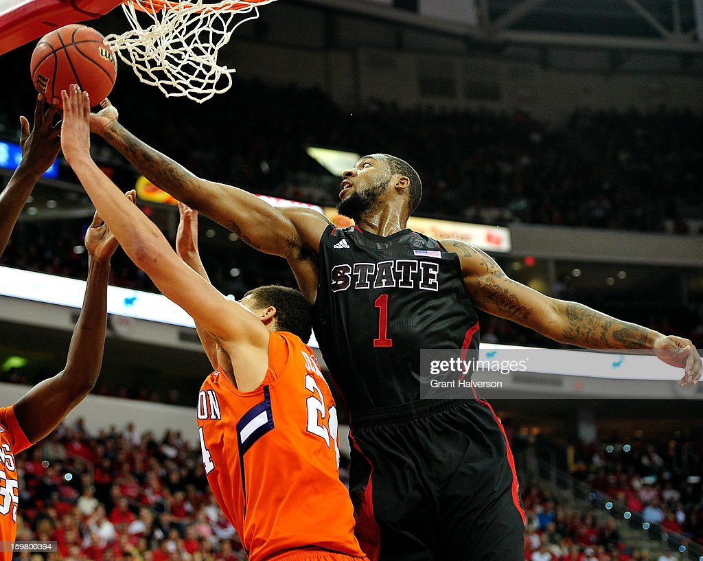 Richard Howell of the North Carolina State Wolfpack tips a rebound away from Milton Jennings of the Clemson Tigers during play at PNC Arena on...