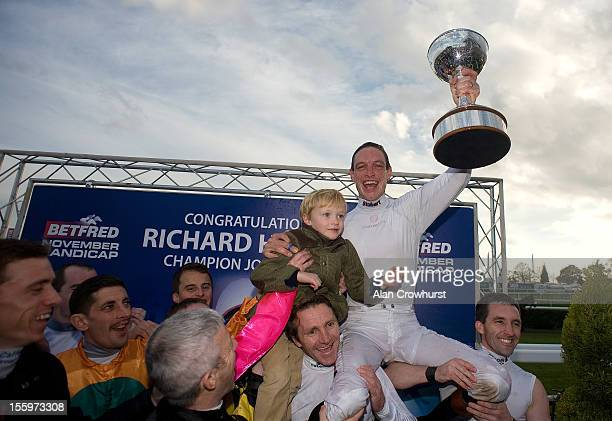 Richard Hughes celebrates winning the 2012 champion jockeys title with son Harvey at Doncaster racecourse on November 10 2012 in Doncaster England