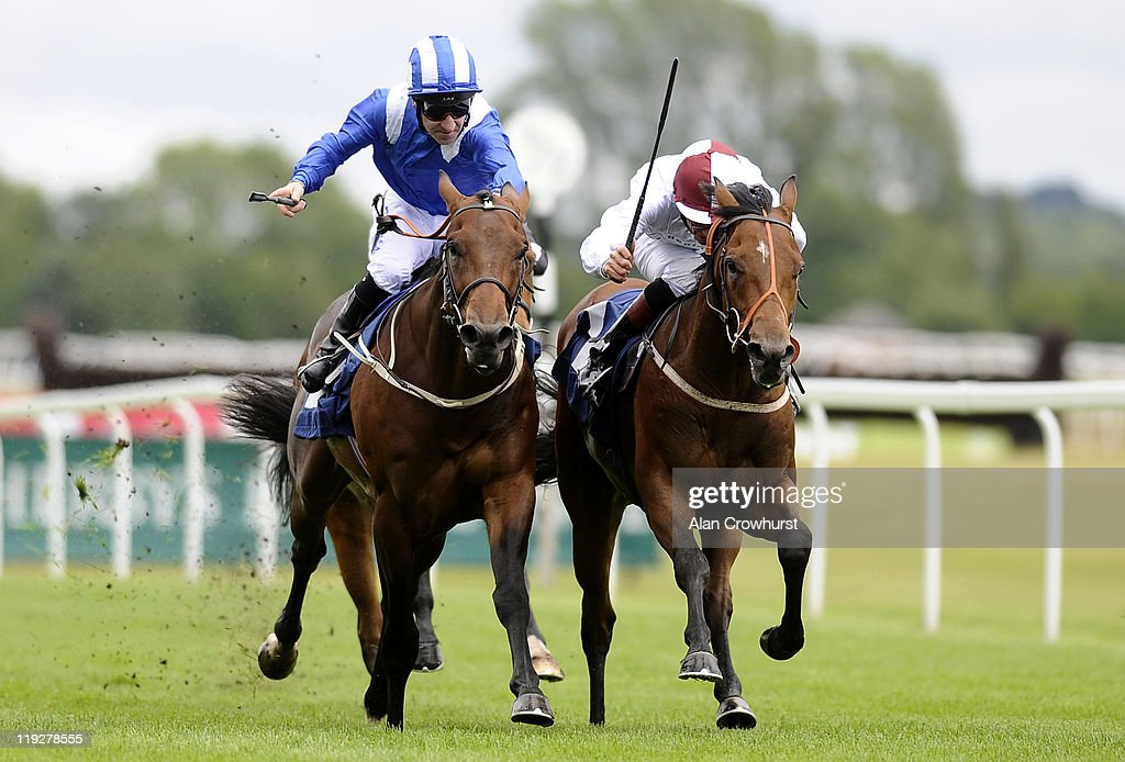 Richard Hughes riding Coupe De Ville (R) win The Trailfinders Conditions Stakes from Leqqaa and Richard Hills (L) at Newbury racecourse on July 16, 2011 in Newbury, England