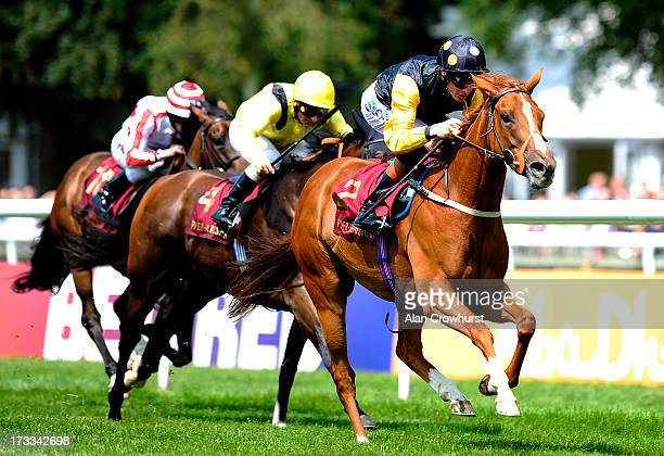 Richard Hughes riding Indignant win The PiperHeidsieck EBF Fillies' Handicap Stakes at Newmarket racecourse on July 12 2013 in Newmarket England