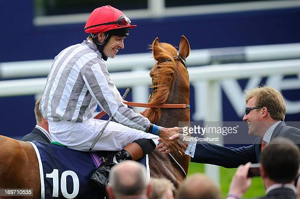 Richard Hughes riding Talent greets trainer Ralph Beckett after winning The Investec Oaks at Epsom racecourse on May 31 2013 in Epsom England