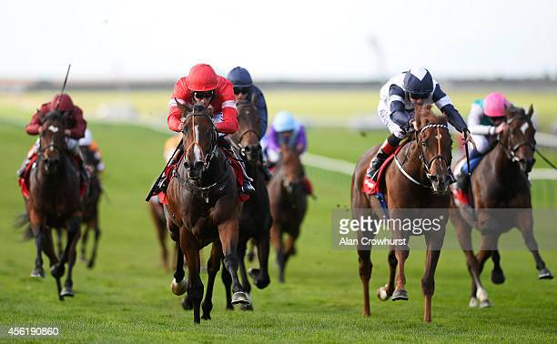 Richard Hughes riding Tiggy Wiggy win The Connolly's Red Mills Cheveley Park Stakes at Newmarket racecourse on September 27 2014 in Newmarket England