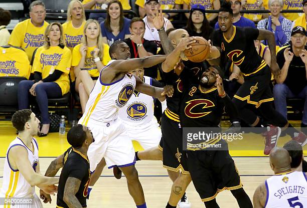 Richard Jefferson and Kyrie Irving of the Cleveland Cavaliers fight for the rebound against Harrison Barnes of the Golden State Warriors during the...