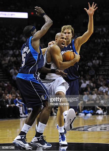Richard Jefferson of the San Antonio Spurs drives to the basket against Josh Howard and Dirk Nowitzki of the Dallas Mavericks during the game at ATT...