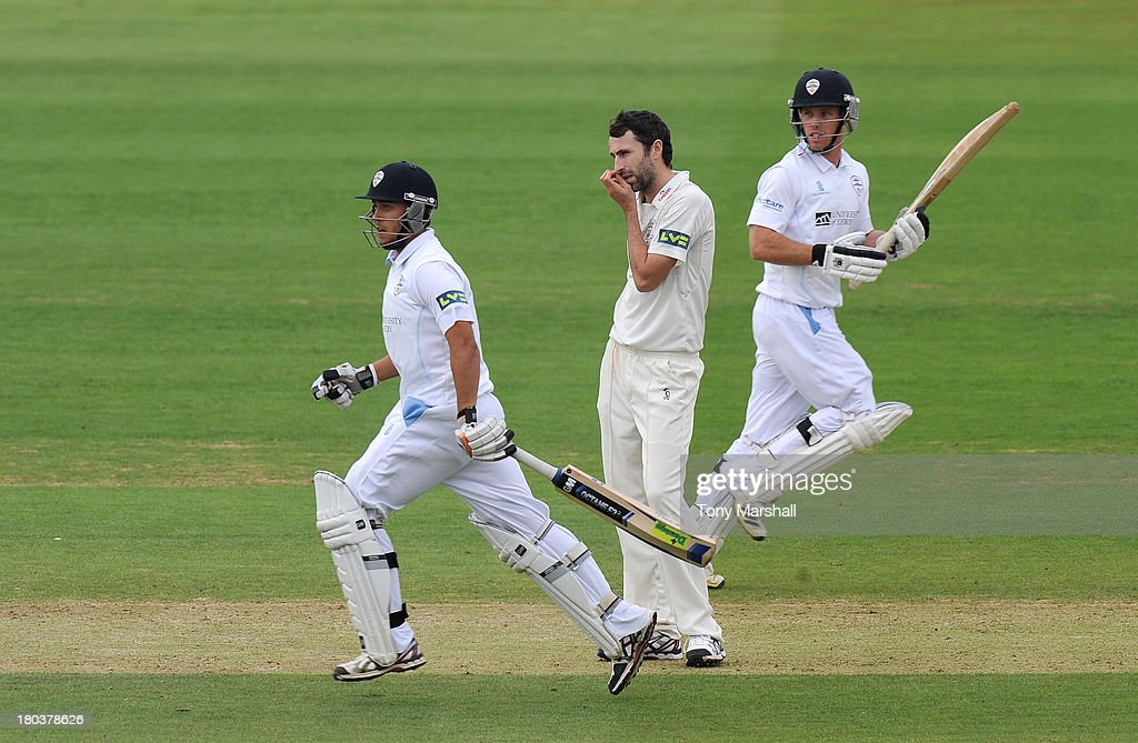 Richard Johnson (L) and Alex Hughes of Derbyshire run between the wickets as Graham Onions of Durham watches the ball head for the boundary during the LV County Championship match between Derbyshire and Durham at The County Ground on September 12, 2013 in Derby, England.