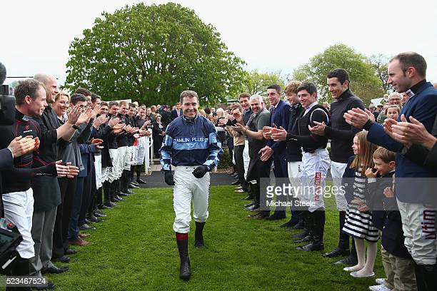 Richard Johnson champion jockey walks into the parade ring as fellow jockeys form a guard of honourat Sandown Park on April 23 2016 in Esher England