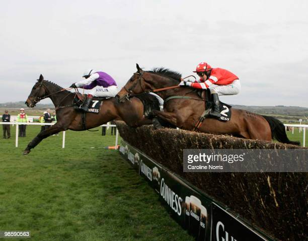 Richard Johnson on Planet Of Sound clears the last fence ahead of Paul Townend on Cooldine to win the Guinness Gold Cup race at Punchestown...