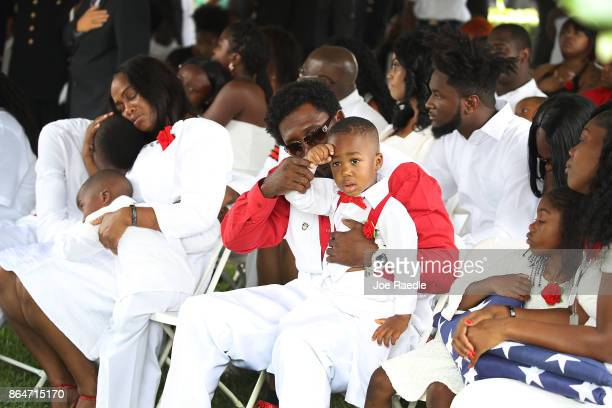 Richard Johnson Sr holds the hand of La David Johnson jr to his forehead for a salute during the burial service for his father US Army Sgt La David...