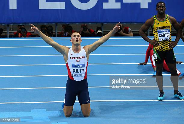 Richard Kilty of Great Britain celebrates winning the gold medal with Nesta Carter of Jamaica in the Men's 60m Final during day two of the IAAF World...