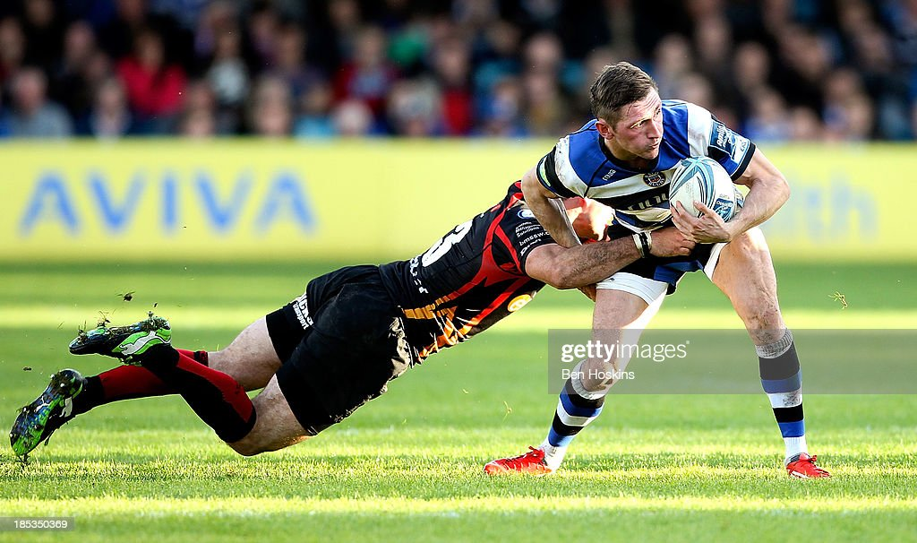 Richard Lane of Bath is tackled by Adam Hughes (L) of Newport during the Amlin Challenge Cup match between Bath and Newport Gwent Dragons at Recreation Ground on October 19, 2013 in Bath, England.