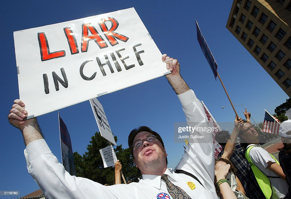Richard Marracq of Palo Alto California carries a sign at a demonstration outside a fundraiser attended by US President George W Bush June 27 2003 in...
