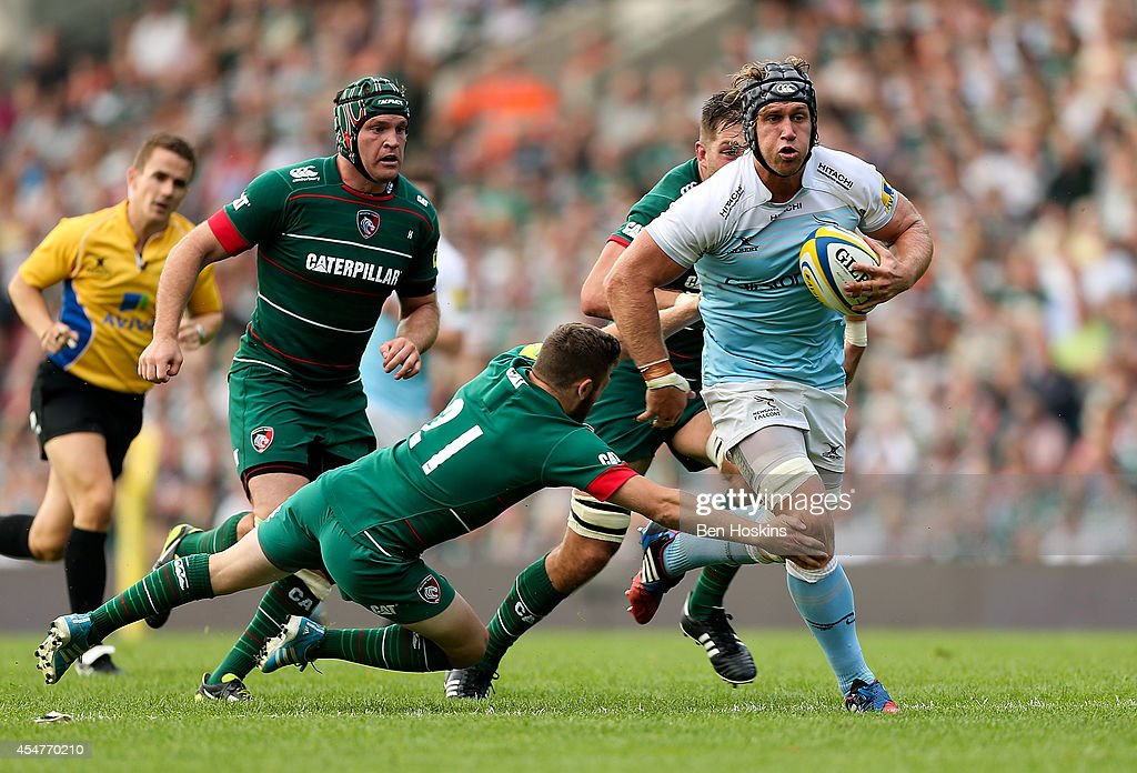 Richard Mayhew of Newcastle is tackled by David Mele of Leicester during the Aviva Premiership match between Leicester Tigers and Newcastle Falcons at Welford Road on September 6, 2014 in Leicester, England.