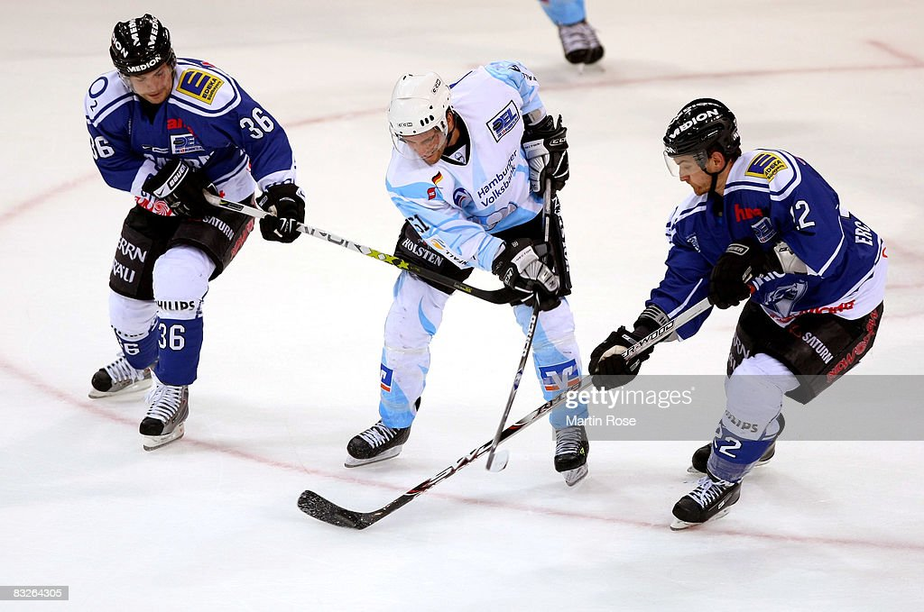 Richard Mueller of Hamburg Eric Nickulas and Michael Bakos of Ingolstadt fight for the puck during the DEL match between Hamburg Freezers and ERC...