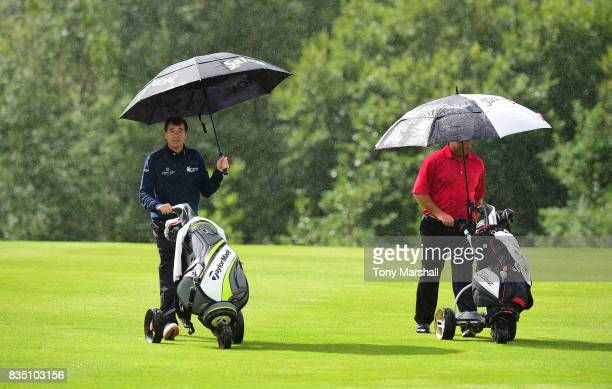 Richard O'Hanlon of St Kew Golf Club and Michael Watson of Wessex Golf Centre walk down the 12th fairway in a rain shower during the Golfbreakscom...