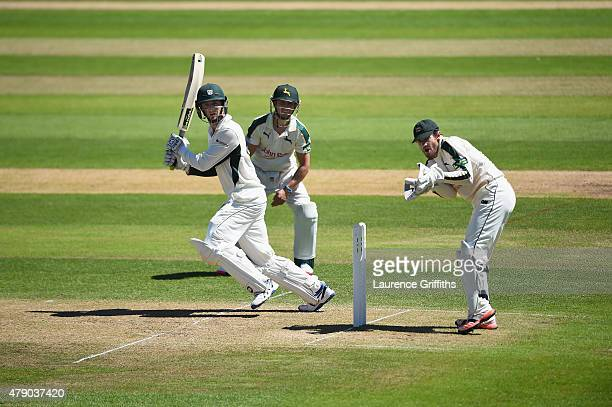 Richard Oliver of Worcestershire hits out to the boundary as Chris Read and James Taylor of Nottinghamshire look on during day two of the LV County...
